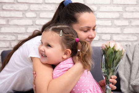 Close-up Of Smiling Cute Daughter Hugging Her Mom Holding Flower Bouquet In Hand At Home Stock Photo