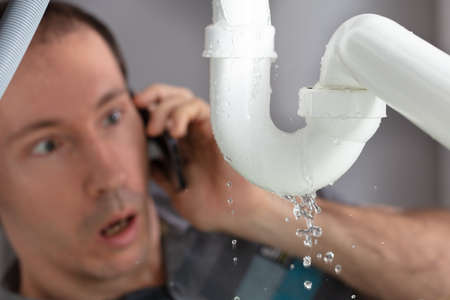 Shocked Young Man Calling Plumber To Fix Sink Pipe Leakage In Kitchen