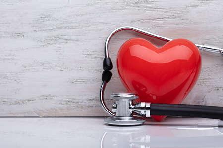 Close-up Of Stethoscope Around Shiny Red Heart On White Desk Reklamní fotografie