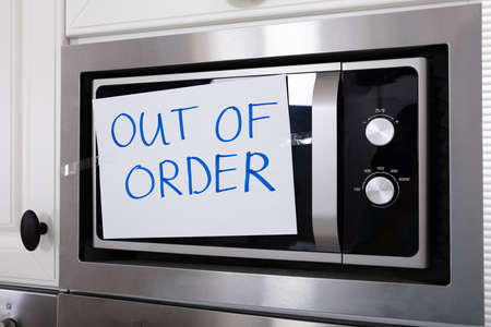 Written Text Out Of Order Message On Paper Over The Stuck Microwave Oven In Kitchen