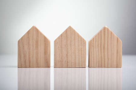 Close-up Of Wooden Houses Arranged In Row On White Desk