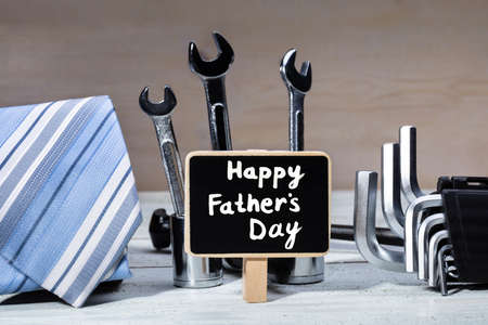 Slate With Happy Fathers Day Text Surrounded With Work Tools And Tie On Wooden Table