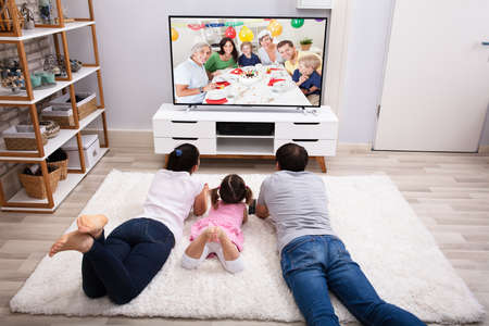 Parents With Their Daughter Lying On Carpet Watching Television At Home Stock Photo