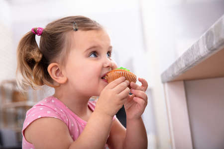 Cute Hungry Girl Taking A Bite Of Delicious Cupcake In The Kitchen