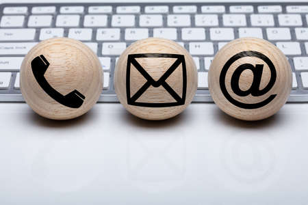 Three Wooden Sphere Shape Ball With Contact Icon In Front Of White Keyboard