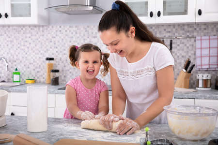 Happy Daughter Helping Her Mother Kneading Dough On Kitchen Counter