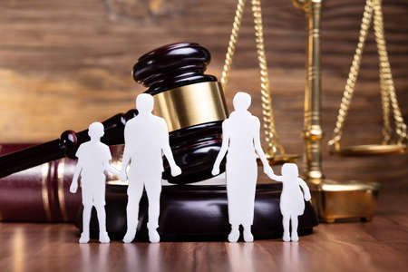 Separation Of Family Figure Cut Out In Front Of Judge Gavel Фото со стока