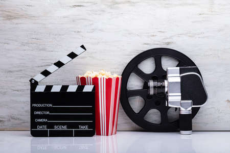 Close-up Of An Movie Camera With Popcorn And Clapper Board Against White Background