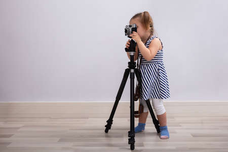Small Innocent Girl Standing On Floor Taking Photo With Camera And Tripod