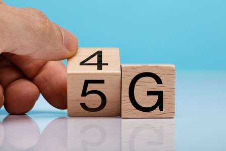 Mans Hand Changing Wooden Block From 4g To 5g On White Surface