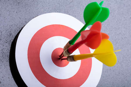 An Elevated View Of Colorful Darts On Target Against Gray Background Фото со стока