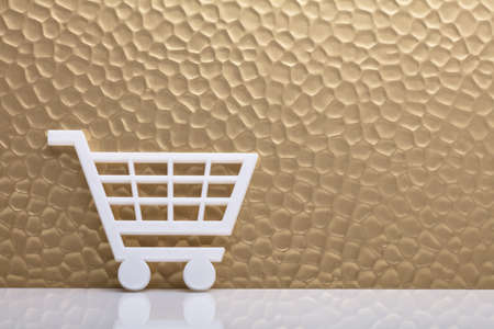 White Shopping Cart Leaning Against Textured Golden Backdrop