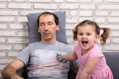 Adorable Child Painting Fathers Face While He Is Sleeping On Sofa