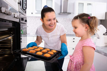 Young Mother Holding Cupcake Tray While Looking At Her Daughter In Kitchen