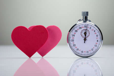 Reflection Of Red And Pink Heart Shape With Stopwatch On White Desk Фото со стока
