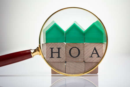 Green House Model Over Homeowner Association Wooden Blocks Seen Through Magnifying Glass Stock Photo