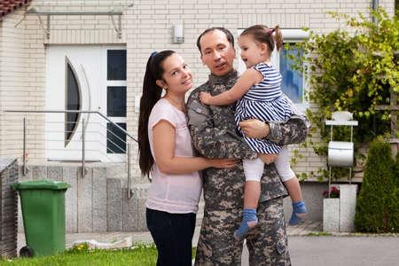 Close-up Of A Happy Soldier Reunited With Family Outside Their Home Фото со стока