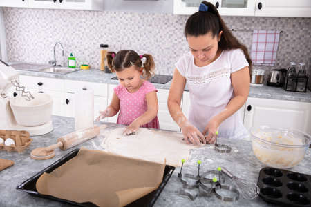 Happy Mother And Daughter Making Cookies With Molds At Kitchen Фото со стока