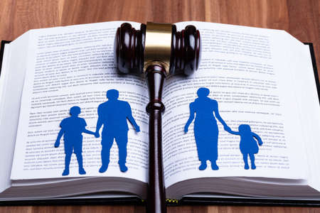 Blue Paper Cutout Of Separated Family On Open Book With Gavel Over Wooden Table Фото со стока