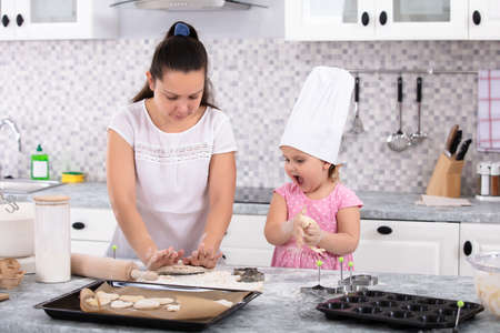 Girl Wearing Chef Hat Helping Her Mother To Make Cookies At Kitchen Фото со стока