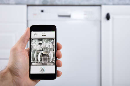 Close-up Of A Persons Hand Operating Dishwasher With Smartphone