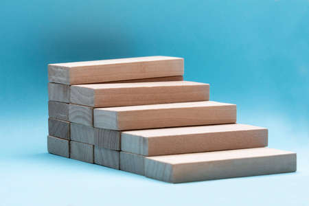 Close-up Of Wooden Building Block Stacked Over Blue Backdrop