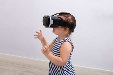 Small Girl Using The Virtual Reality Headset On White Background