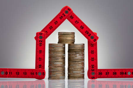 Stack Of Coins Under The House Made With Red Measuring Tape On The Desk