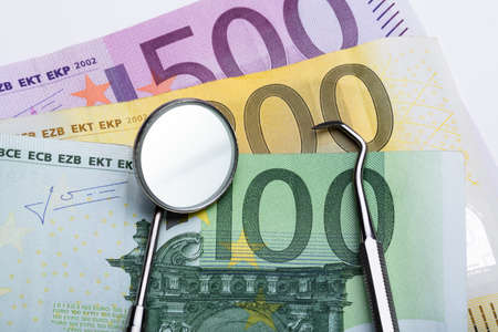 An Overhead View Of Dental Tools On Euro Notes