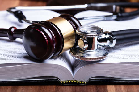 Close-up Of Stethoscope And Mallet Over Opened Law Book On Wooden Desk Фото со стока