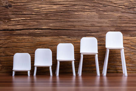 Empty Miniature Increasing Scale Of White Chair On Wooden Background Фото со стока