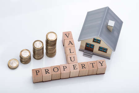 House Model And Stacked Coins Showing Property Value Concept On Reflective Desk