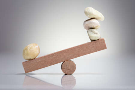 Pebble Stones Balancing On Wooden Seesaw Over The White Background