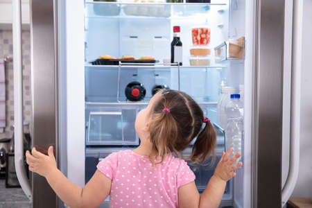 Rear View Of Girl Standing In Kitchen Opening Fridge Door Looking Inside