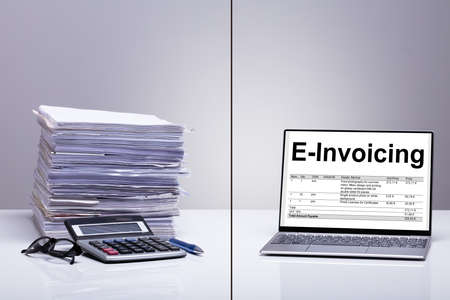 Stacked Of E-invoice Paper And Calculator Is Replace With New Technology Against White Background