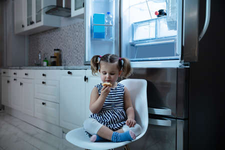 Cute Little Girl Eating Cupcake While Sitting In Front Of Open Refrigerator In Kitchen