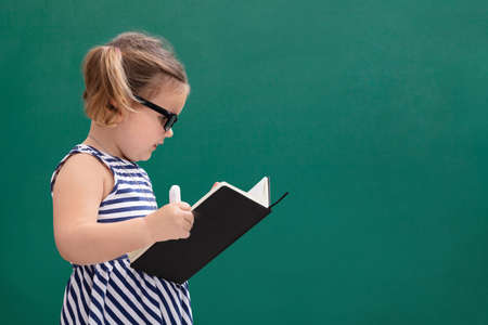 Cute Little Girl Standing In Front Of Chalkboard Reading Book