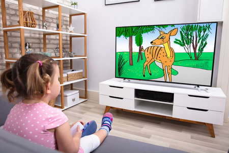 Rear View Of Innocent Girl Sitting On Sofa Watching Cartoon On Television