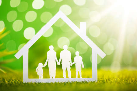 Close-up Of Paper Cut Out Of Family House On Grassy Field Фото со стока