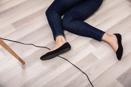An Elevated View Of Woman Stumbling With An Electrical Cord