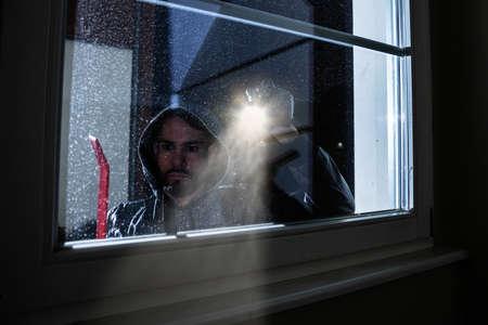 Burglar With Crowbar And Flashlight Looking Into A House Windows