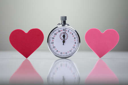 Reflection Of Red And Pink Heart Shape With Stopwatch On White Desk Stock Photo