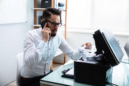 Joven empresario llamando por teléfono móvil quitando papel atascado en la impresora Foto de archivo