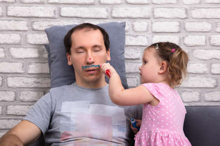 Little Girl Painting Father's Face While He Sleeping On Couch At Home