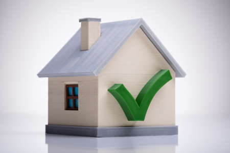 Miniature House Model With Green Tick Mark On White Desk