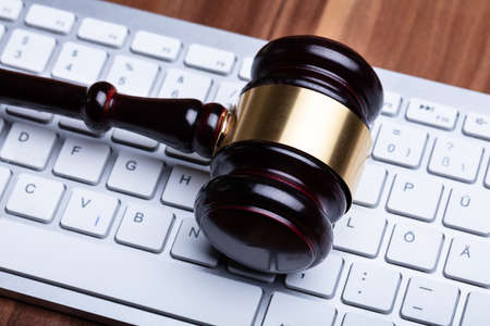 Close-up Photo Of Wooden Gavel On Keyboard Stock Photo