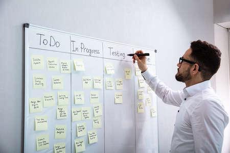 사무실에서 화이트 보드에 첨부 된 스티커 메모에 작성 하는 사업가의 측면 보기