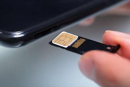 Close-up de la mano de una persona insertando la tarjeta SIM en el teléfono móvil Foto de archivo