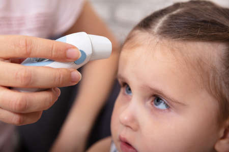 Mother Checking Fever Of Her Sick Daughter Using Forehead Thermometer At Home