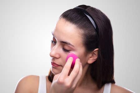 Beautiful Young Woman Applying Makeup Using Pink Blender Sponge